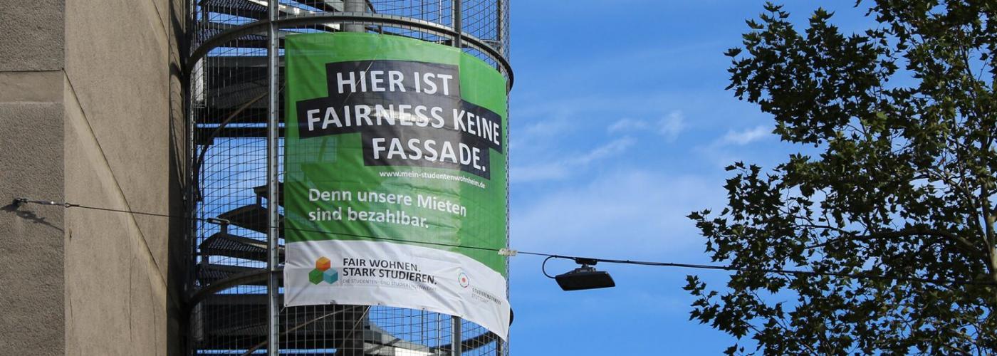 Eine Außentreppe an einem Gebäude an der ein grünes Banner hängt